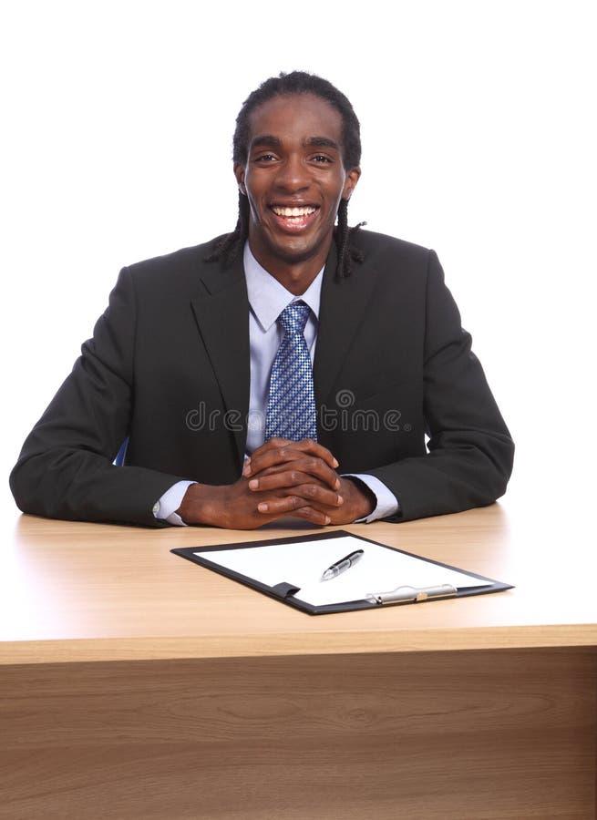 El hombre de negocios negro joven feliz se sienta al escritorio de oficina fotos de archivo