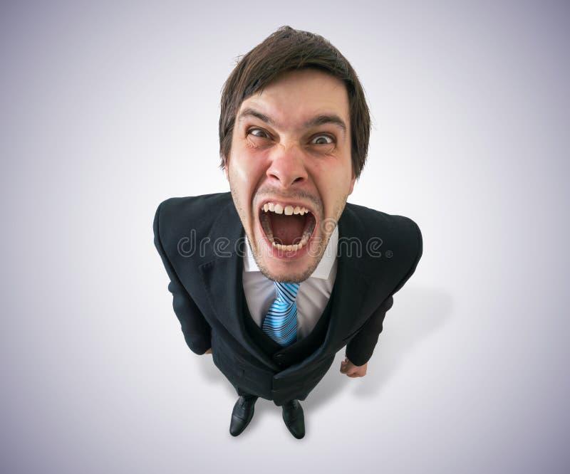 El hombre de negocios o el jefe enojado divertido joven está gritando Visión desde la tapa fotografía de archivo