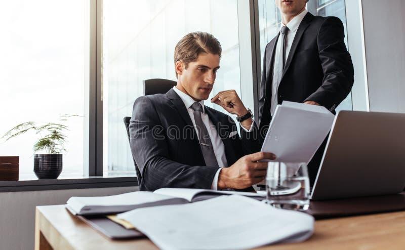 El hombre de negocios partners la lectura de un cierto papeleo foto de archivo libre de regalías