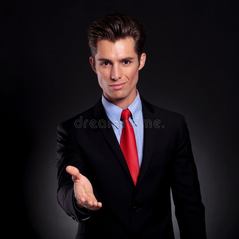 El hombre de negocios pone hacia fuera la mano fotos de archivo