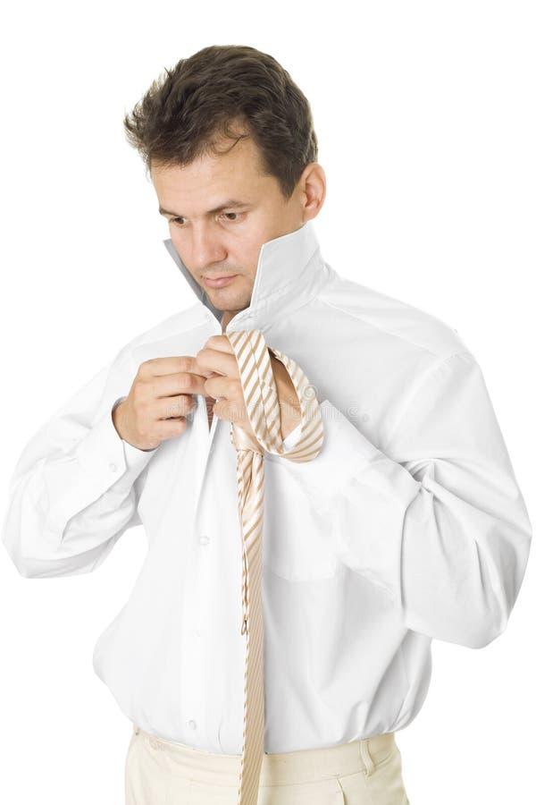 El hombre de negocios pone una camisa y un lazo foto de archivo