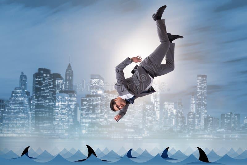 El hombre de negocios que cae en el mar con los tiburones foto de archivo