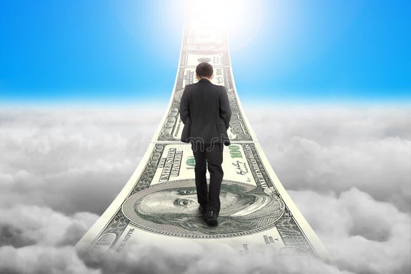El hombre de negocios que camina en las escaleras del dinero con luz del sol del cielo se nubla imagenes de archivo