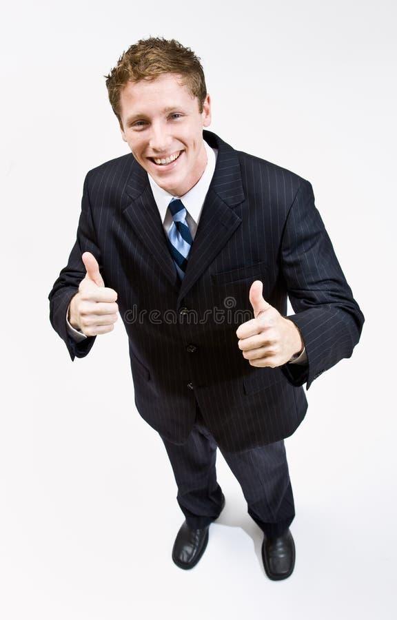 El hombre de negocios que da los pulgares sube gesto foto de archivo
