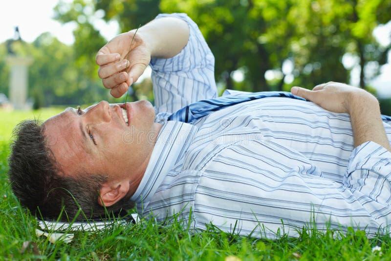 El hombre de negocios que descansa la mentira al aire libre encendido apoya en el parque fotografía de archivo