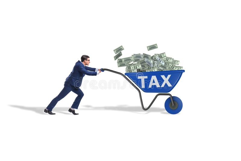 El hombre de negocios que empuja la carretilla por completo del dinero en concepto del impuesto fotografía de archivo libre de regalías