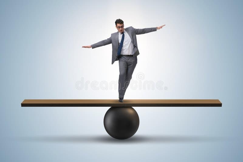 El hombre de negocios que intenta equilibrar en bola y la oscilación fotos de archivo libres de regalías