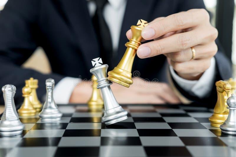 El hombre de negocios que juega la figura del ajedrez toma a jaque mate otro rey con el equipo, triunfo de la estrategia o de la  imagen de archivo libre de regalías