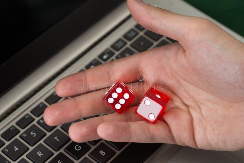 El hombre de negocios que lleva a cabo rojo corta en cuadritos mientras que usa el ordenador portátil fotografía de archivo libre de regalías