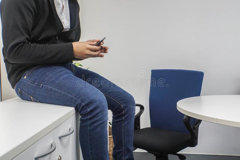 El hombre de negocios que lleva a Jean se sienta en el escritorio usando smartphone en oficina fotografía de archivo libre de regalías