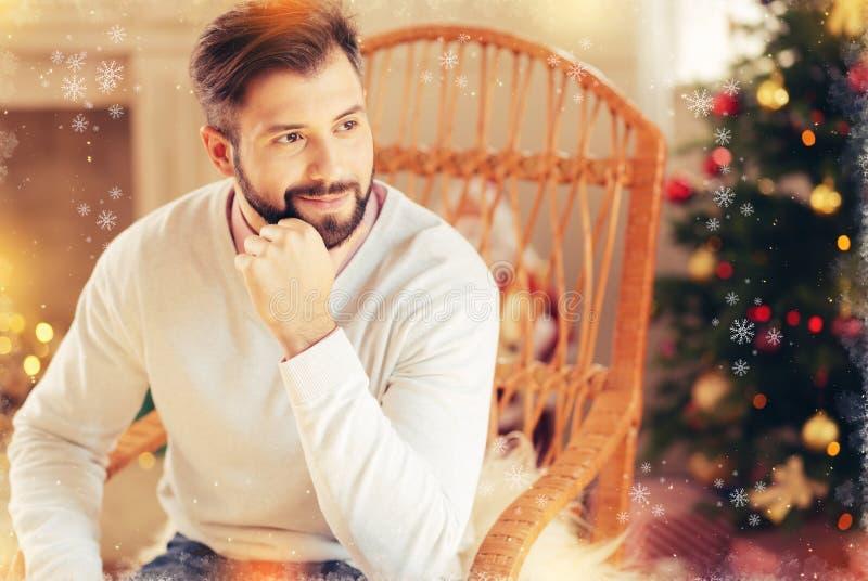 El hombre de negocios que llevaba la sensación beige del suéter descansó sentarse cerca del árbol de navidad imagen de archivo libre de regalías