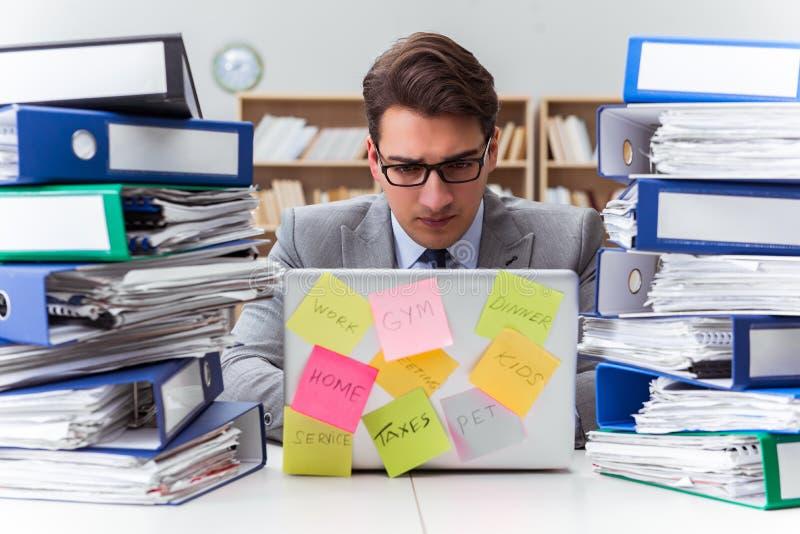 El hombre de negocios que lucha con prioridades múltiples imagen de archivo