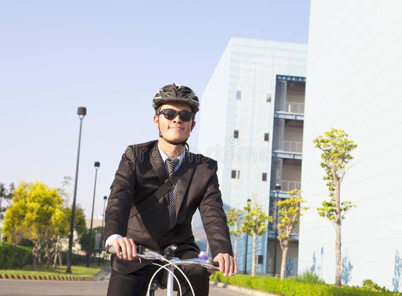 El hombre de negocios que monta una bicicleta al lugar de trabajo para proteger rodea imagen de archivo