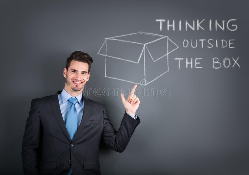 El hombre de negocios que muestra un dibujo de piensa fuera de la caja fotos de archivo libres de regalías
