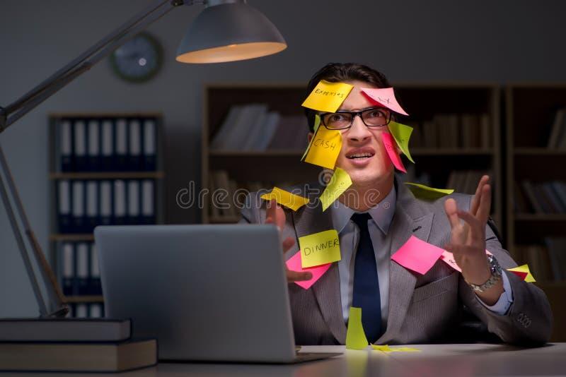 El hombre de negocios que permanece tarde para arreglar prioridades foto de archivo libre de regalías