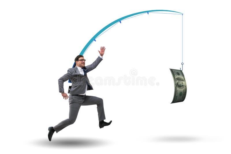 El hombre de negocios que persigue el dinero en la caña de pescar fotografía de archivo libre de regalías