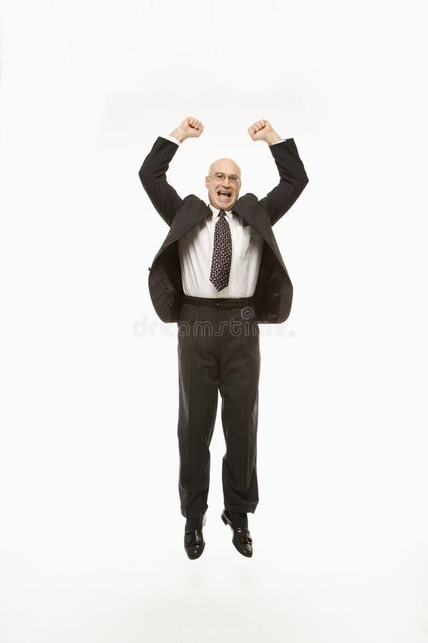 El hombre de negocios que salta con los brazos levantados. imagenes de archivo