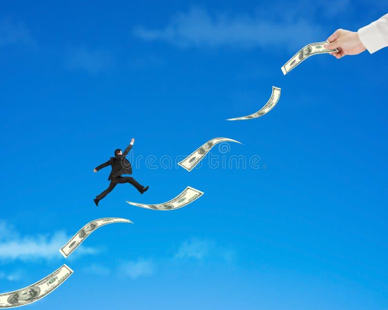 El hombre de negocios que salta en el dinero con el control uno de la mano fotografía de archivo