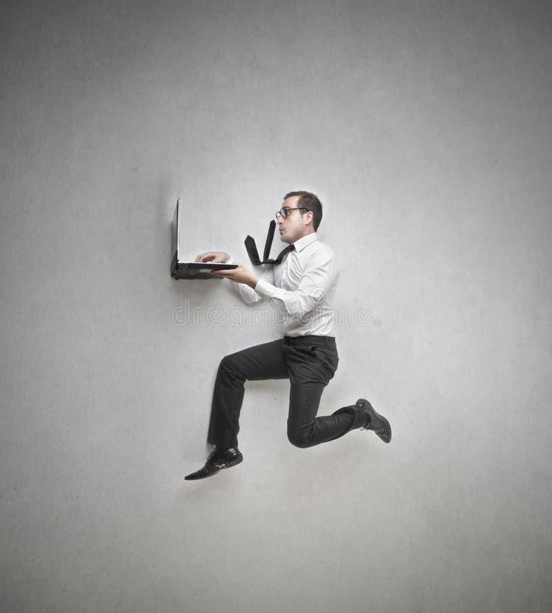 El hombre de negocios que salta mientras que trabaja fotos de archivo libres de regalías