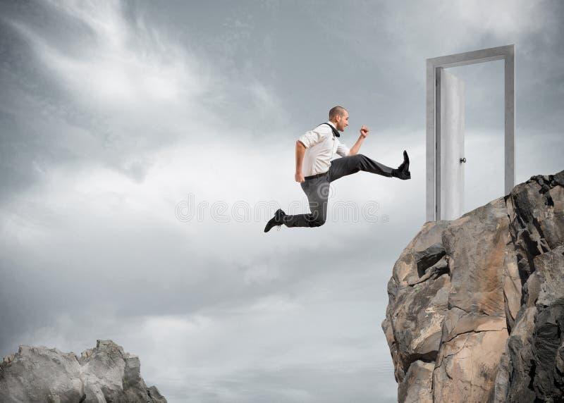 El hombre de negocios que salta sobre las montañas para alcanzar una puerta fotos de archivo libres de regalías