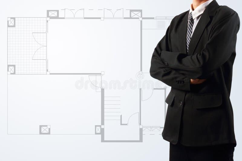 El hombre de negocios que se coloca cerca de una casa blueprints ilustración del vector