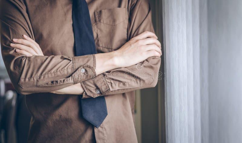 El hombre de negocios que se coloca de pensamiento y cruza un brazo del ` s cerca de ventana imágenes de archivo libres de regalías