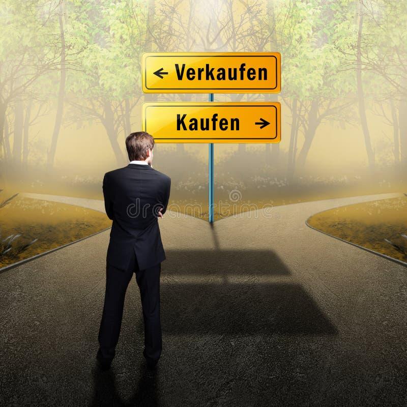 El hombre de negocios que se coloca en un cruce, teniendo que elegir la trayectoria derecha qué hacer con las palabras vende y co imagen de archivo
