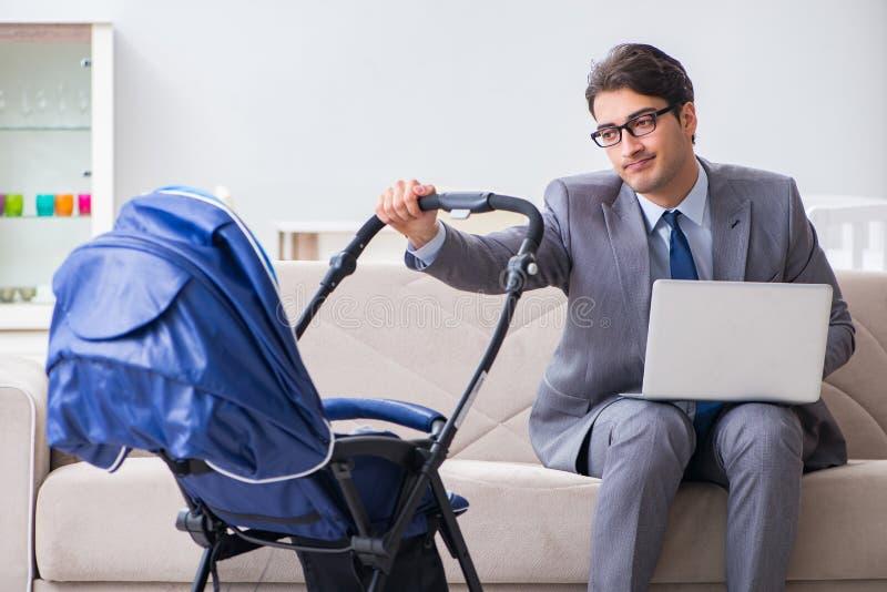 El hombre de negocios que se ocupa al bebé recién nacido en casa y que trabaja en casa imagen de archivo