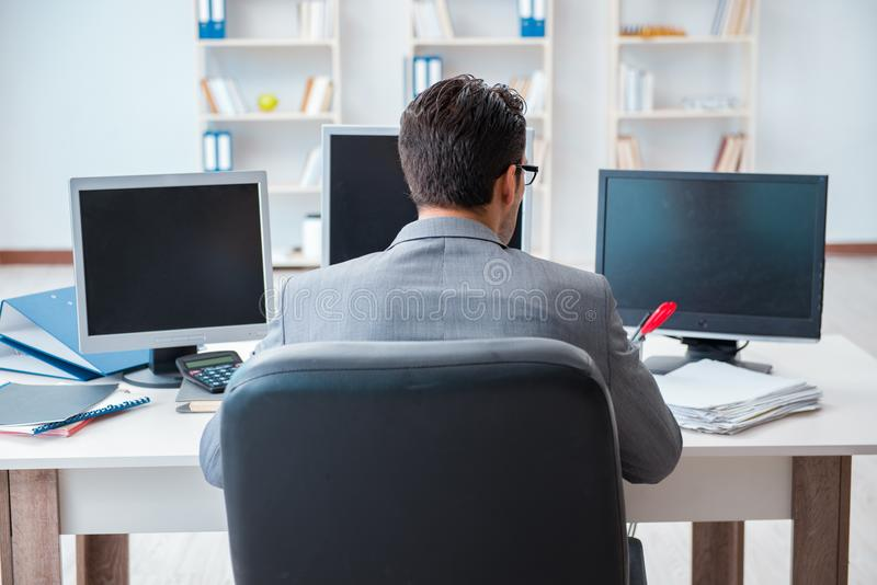 El hombre de negocios que se sienta delante de muchas pantallas foto de archivo libre de regalías