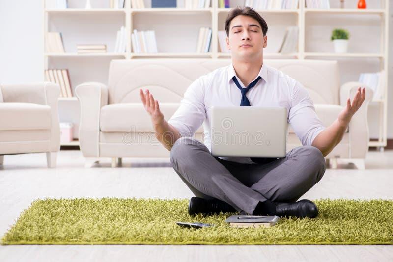 El hombre de negocios que se sienta en el piso en oficina imagenes de archivo