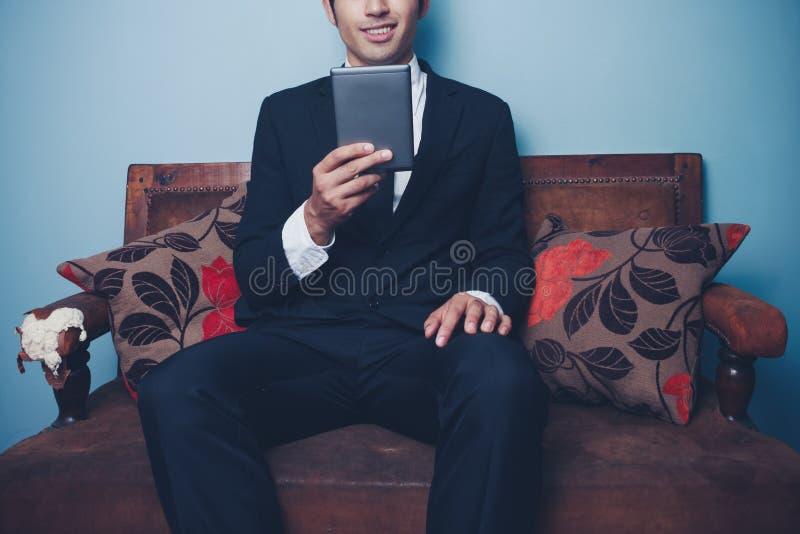 El hombre de negocios que se sienta en el sofá está leyendo informe financiero en la tabla fotos de archivo libres de regalías