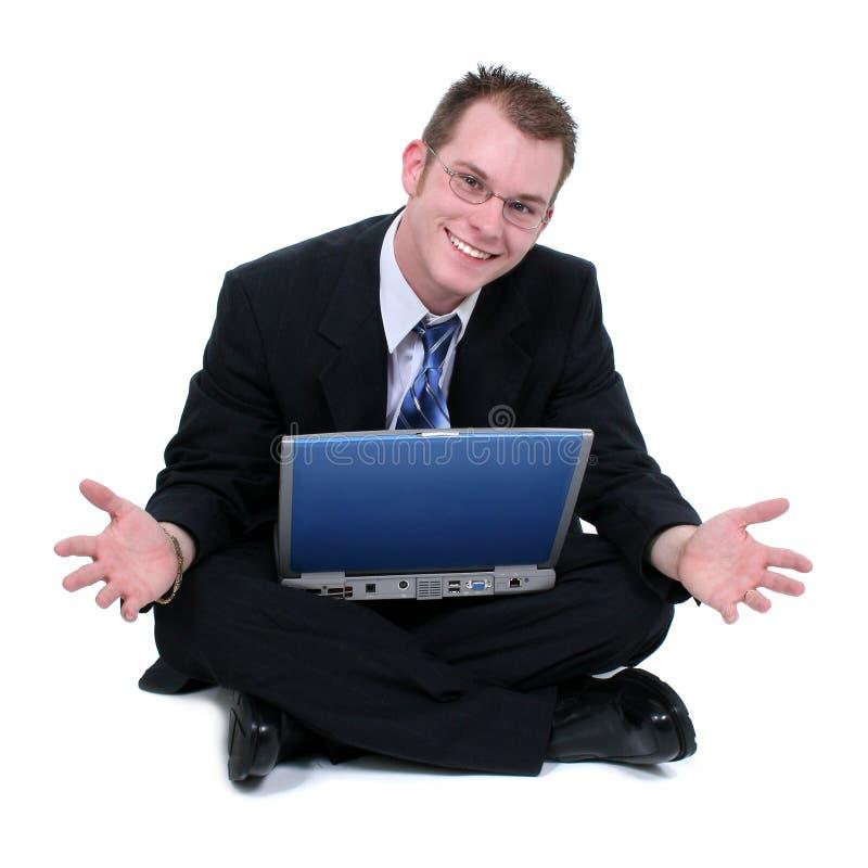 El hombre de negocios que se sienta en suelo con la computadora portátil reparte foto de archivo libre de regalías