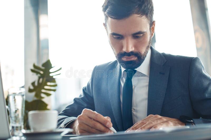 El hombre de negocios que se sienta en una escritura del restaurante del centro de negocios documenta el primer imagen de archivo