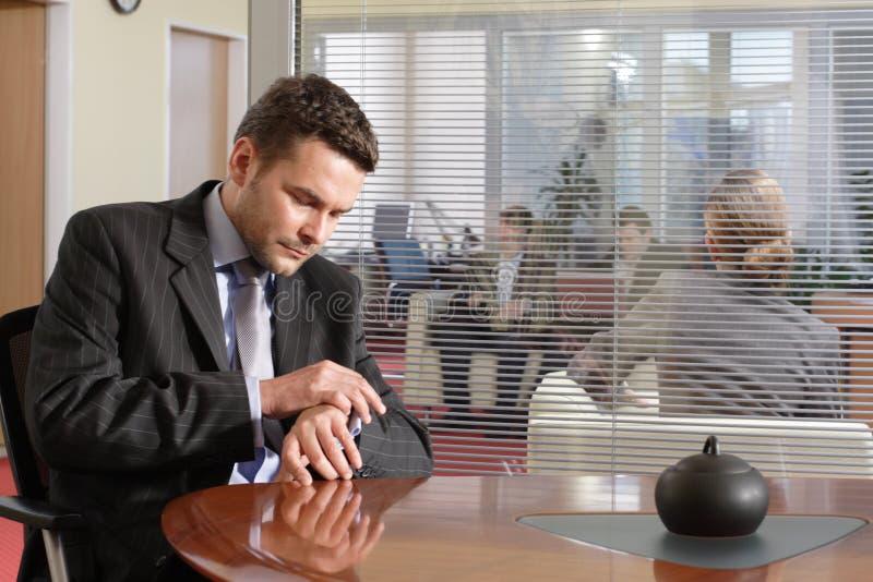 El hombre de negocios que se sienta maduro hermoso está controlando tiempo foto de archivo