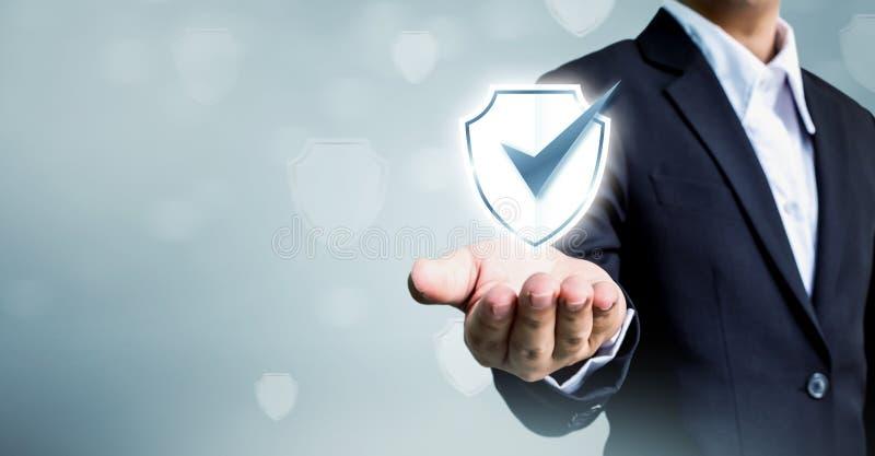 El hombre de negocios que sostiene el escudo protege el icono, seguridad cibernética del concepto imágenes de archivo libres de regalías