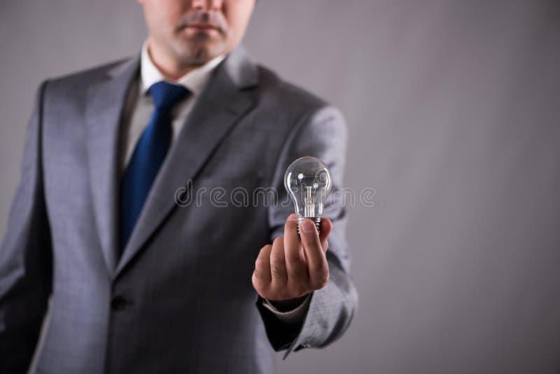 El hombre de negocios que sostiene la bombilla en concepto de la creatividad fotografía de archivo libre de regalías