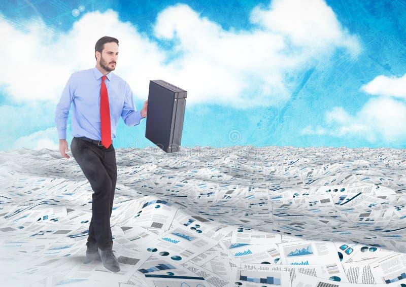 El hombre de negocios que sostiene la cartera en el mar de documentos debajo del cielo se nubla fotografía de archivo