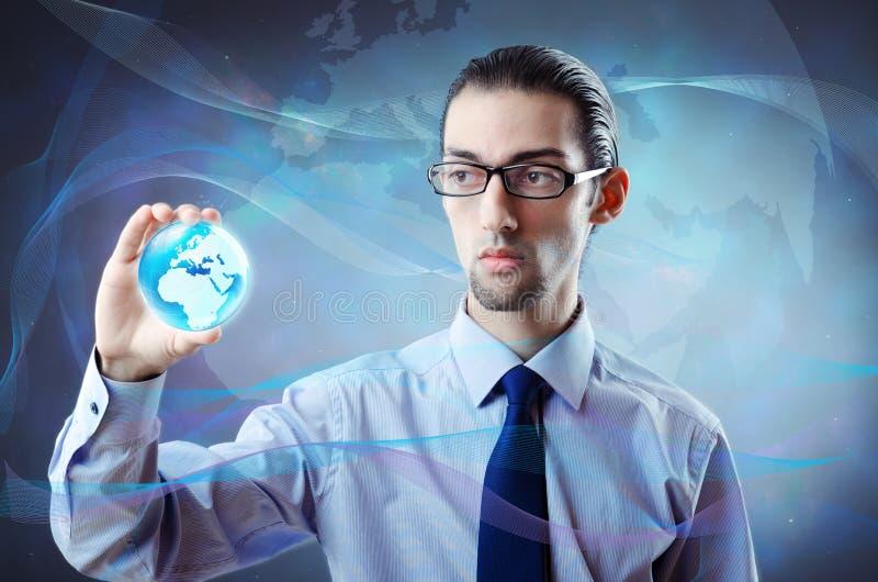 El hombre de negocios que sostiene la tierra en concepto global imagen de archivo