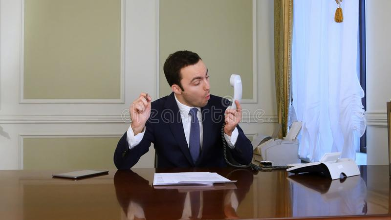 El hombre de negocios que tiene problema mientras que llama por teléfono y pone el teléfono abajo foto de archivo