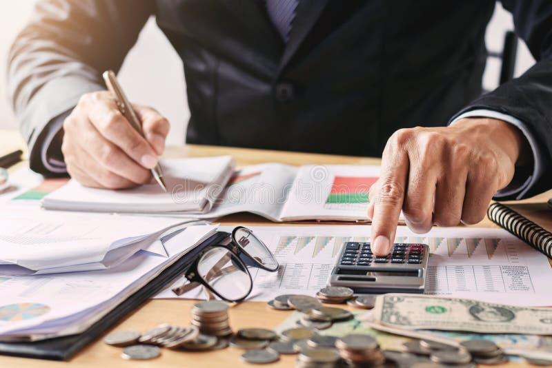 el hombre de negocios que trabaja en oficina usando la calculadora para calcula el presupuesto fotos de archivo
