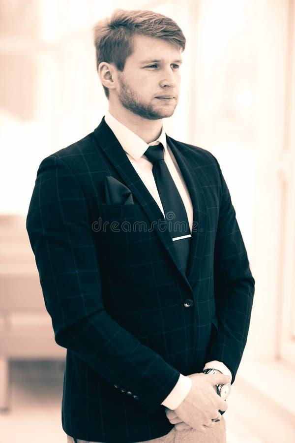 El hombre de negocios el reci?n llegado en un traje de negocios se coloca cerca de la ventana, fotografía de archivo libre de regalías