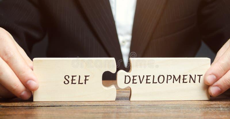 El hombre de negocios recoge rompecabezas con el autodesarrollo de la palabra Concepto de nuevas habilidades y motivación del neg imagen de archivo