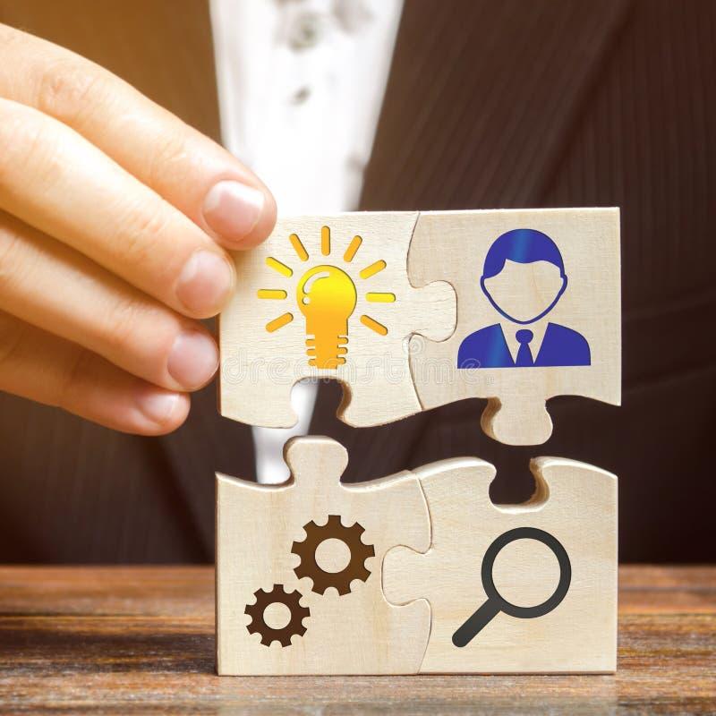 El hombre de negocios recoge rompecabezas con la imagen de las cualidades de hacer negocio Concepto del planeamiento de la estrat fotografía de archivo libre de regalías