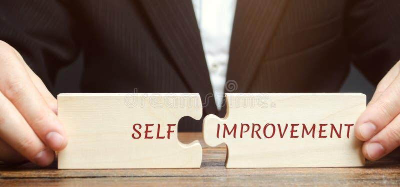 El hombre de negocios recoge rompecabezas con la Uno mismo-mejora de la palabra Concepto de nuevas habilidades y motivación del n imagenes de archivo