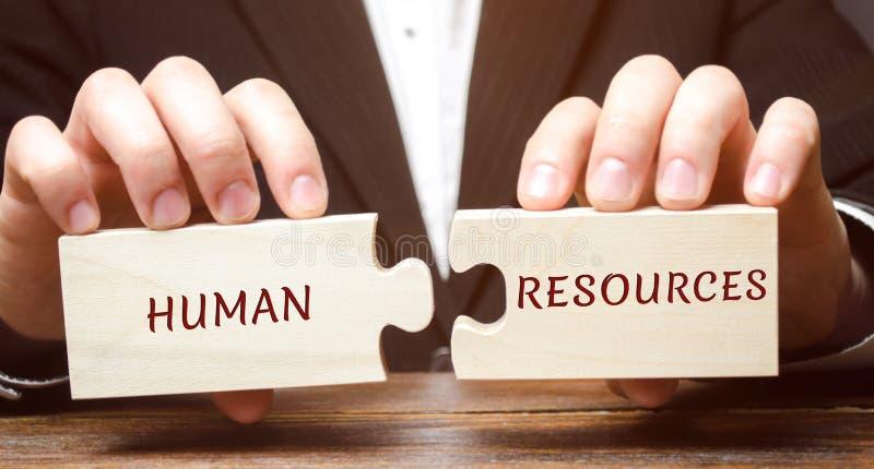 El hombre de negocios recoge rompecabezas de madera con los recursos humanos de la palabra Reclutamiento, hora, dirección y el te foto de archivo libre de regalías