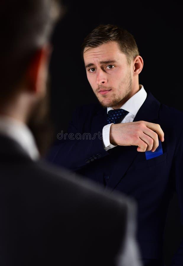 El hombre de negocios saca la tarjeta de crédito del bolsillo Concepto de la compra Hombres en la reunión formal de los trajes pa foto de archivo