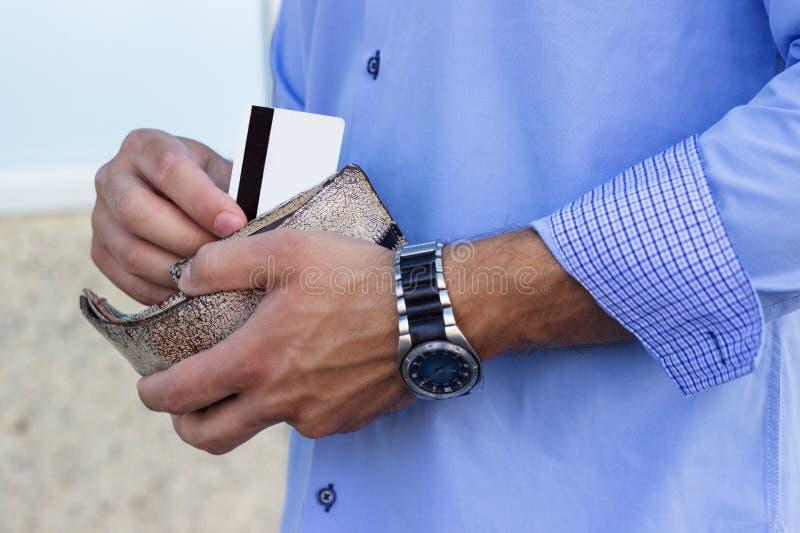 El hombre de negocios saca una tarjeta de crédito de la cartera fotografía de archivo libre de regalías