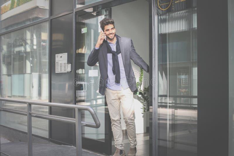 El hombre de negocios sale el edificio y hablar en el pH móvil foto de archivo