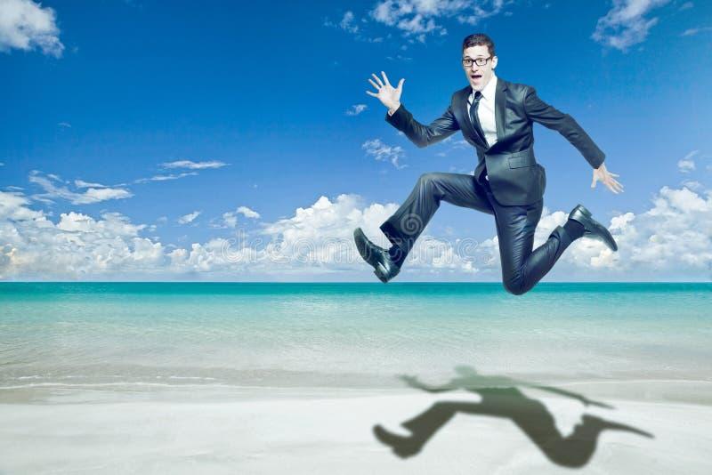 El hombre de negocios salta en juego negro en la playa tropical. imagenes de archivo