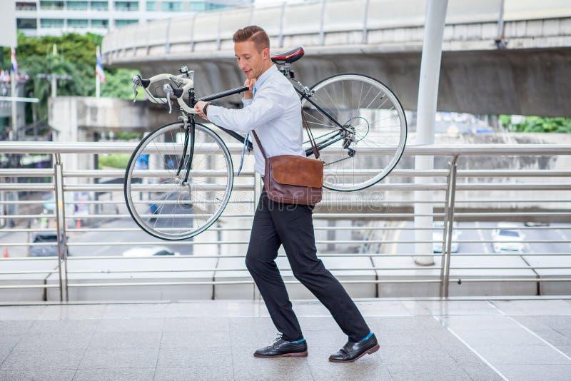 el hombre de negocios se apresura para arriba y llevando su bicicleta para mirar el reloj que comprueba hora a atrasado en las ca imágenes de archivo libres de regalías